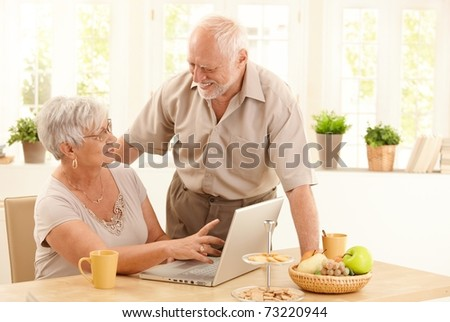 Happy senior couple using laptop computer at home, wife pointing at screen, husband laughing at wife.? - stock photo