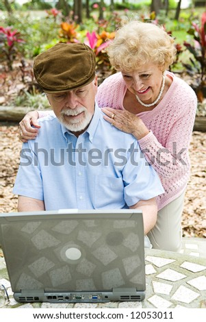 Happy senior couple using their laptop computer outdoors.  Focus on husband. - stock photo