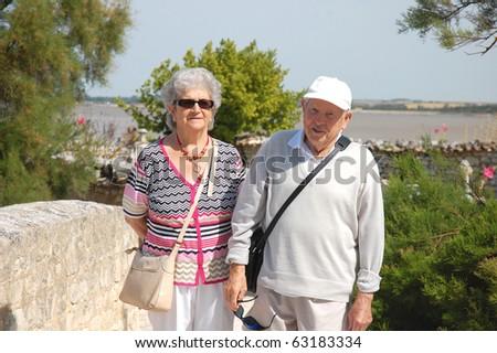 Happy senior couple walking along the coast of Brittany - stock photo