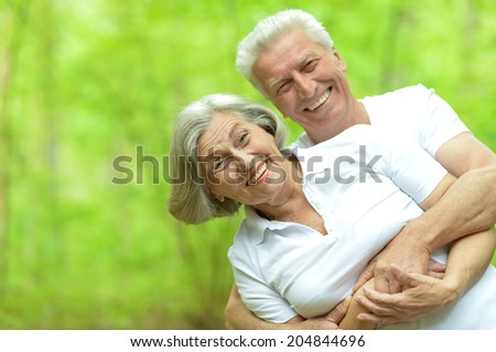 happy senior couple walking in summer forest - stock photo