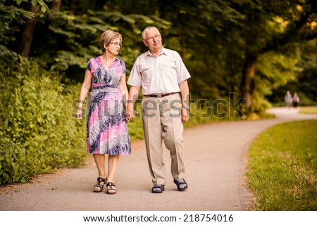 Happy senior couple walking together holding hands in forest park - stock photo