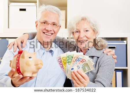 Happy senior couple with fan of Euro money and a piggy bank - stock photo