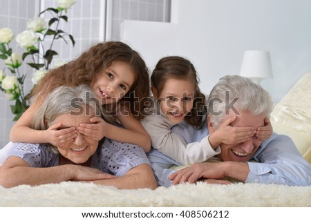 Happy senior couple with grandchildren - stock photo