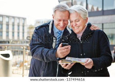 Happy senior couple with map and city guide app on smartphone - stock photo