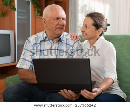 Happy senior couple  with notebook in home