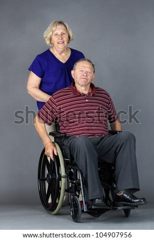 Happy senior couple with old man in a wheelchair, studio shot on grey. - stock photo