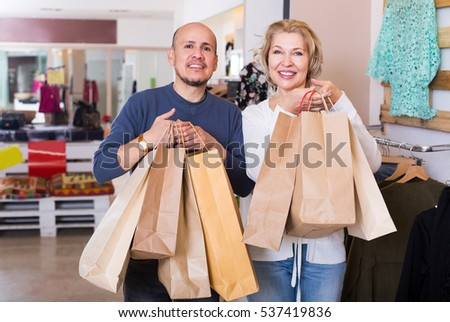 Happy senior couple with purchases in bags at apparel store