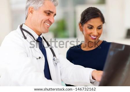 happy senior doctor examining patient's x-ray  - stock photo