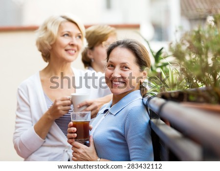 Happy senior female colleagues having lunch break at patio and drinking tea - stock photo