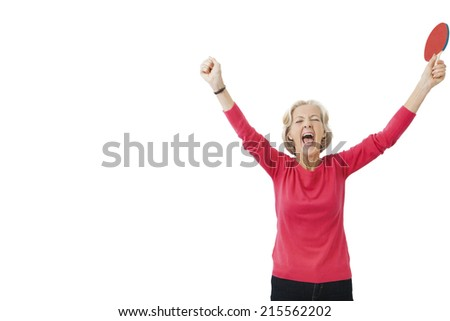 Happy senior female table tennis player with arms raised celebrating victory - stock photo