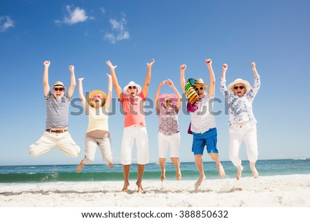 Happy senior friends jumping on the beach - stock photo