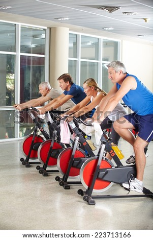 Happy senior group exercising in class in a gym - stock photo