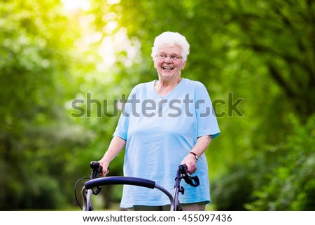 Happy senior handicapped lady with a walking disability enjoying a walk in a sunny park pushing her walker or wheel chair, aid and support during retirement concept. - stock photo