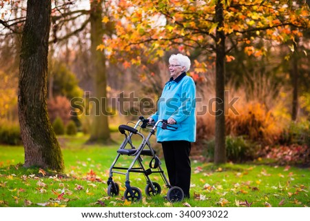 Happy senior handicapped lady with a walking disability enjoying a walk in an autumn park pushing her walker or wheel chair. Aid and support during retirement. Patient of nursing home or care center. - stock photo