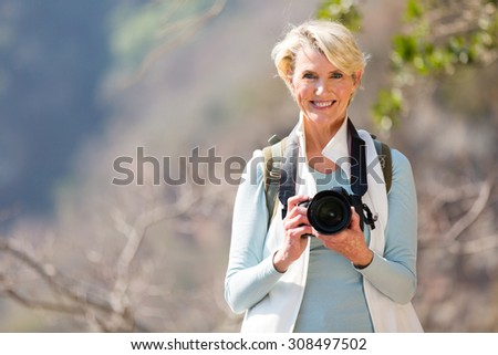 happy senior hiker standing on top of the mountain - stock photo