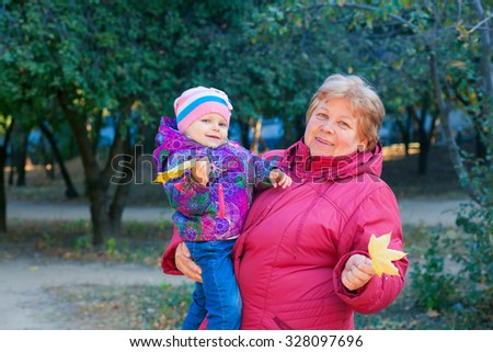 Happy senior lady and a little toddler girl, grandmother and granddaughter, enjoying a walk in the park. Child and  grandparent. autumns day. Grandmother and little girl happy together in the garden - stock photo