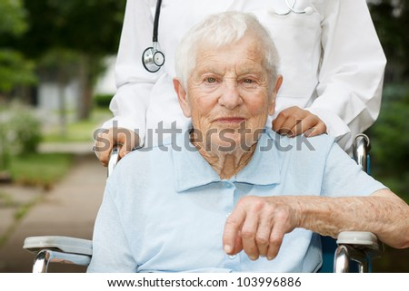 Happy senior lady in wheelchair with her caregiver - stock photo