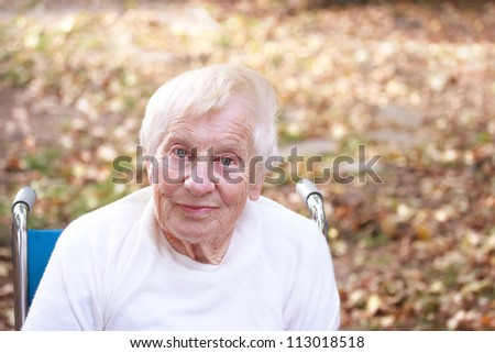 Happy senior lady smiling outside in autumn