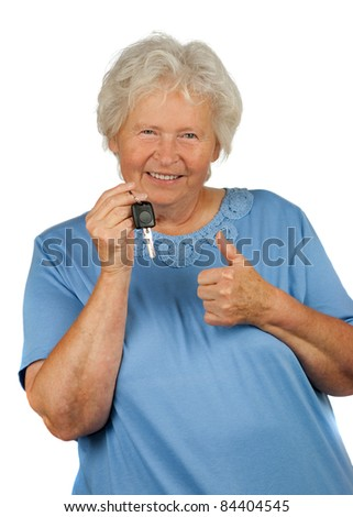 happy senior lady with a car key is making OK gesture - stock photo