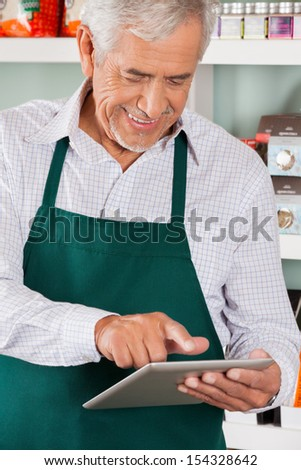 Happy senior male owner using digital tablet in grocery store - stock photo