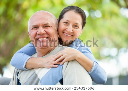 Happy senior man and mature woman together against blured trees of park or forest - stock photo