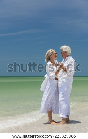 Happy senior man and woman couple dancing and holding hands on a deserted tropical beach with bright clear blue sky - stock photo