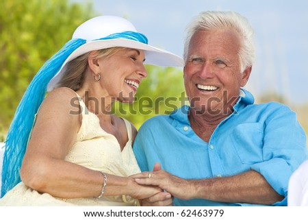 Happy senior man and woman couple having fun together holding hands and laughing on a deserted tropical beach. - stock photo