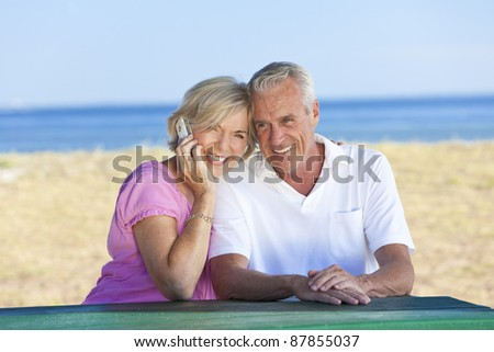 Happy senior man and woman couple sitting together at a table by a beach talking on a cell phone - stock photo