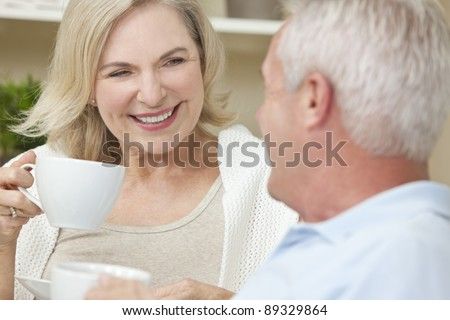 Happy senior man and woman couple sitting together at home smiling and drinking tea or coffee