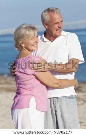 Happy senior man and woman couple together embracing and walking on a deserted tropical beach - stock photo