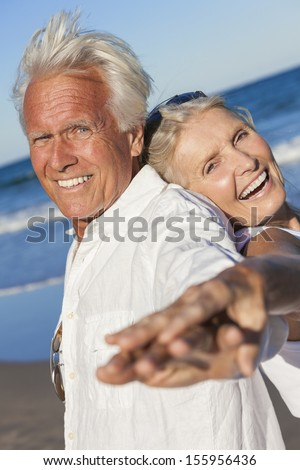 Happy senior man and woman couple together laughing back to back by blue sea on a deserted tropical beach with bright clear blue sky - stock photo