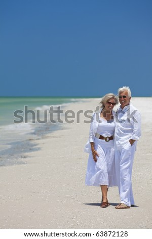 Happy senior man and woman couple together laughing on a deserted tropical beach with bright clear blue sky.