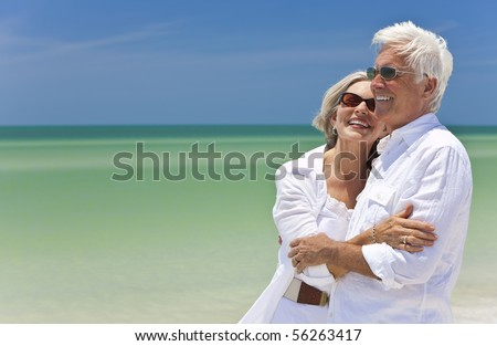 Happy senior man and woman couple together looking out to sea on a deserted tropical beach with bright clear blue sky - stock photo