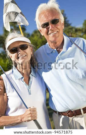 Happy senior man and woman couple together playing golf - stock photo