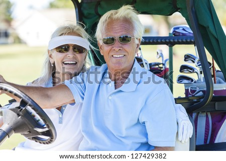 Happy senior man and woman couple together playing golf driving the golf cart or buggy on the course