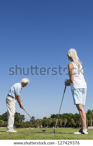 Happy senior man and woman couple together playing golf on a course near a lake they are at the tee driving down the fairway - stock photo