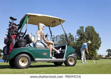 Happy senior man and woman couple together playing golf, the man is hitting a shot the woman is sitting in a golf cart - stock photo