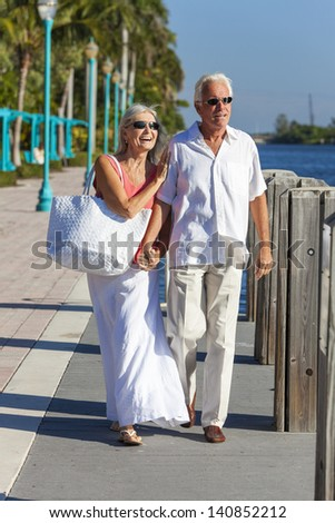 Happy senior man and woman romantic couple walking together, holding hands & looking out to tropical sea or river with bright clear blue sky - stock photo