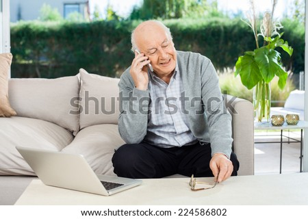 Happy senior man answering smartphone while sitting on couch at nursing home porch - stock photo