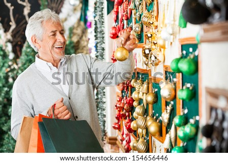 Happy senior man choosing Christmas balls at store