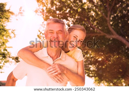 Happy senior man giving his partner a piggy back in the city on a sunny day - stock photo
