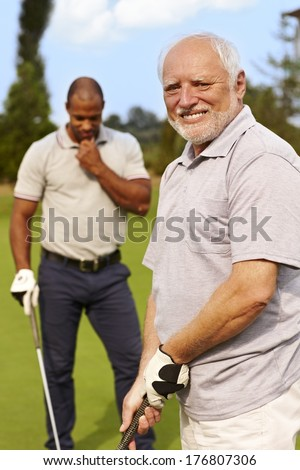 Happy senior man golfing, smiling.