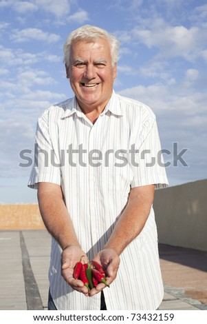 Happy senior man holding chilipeppers. - stock photo