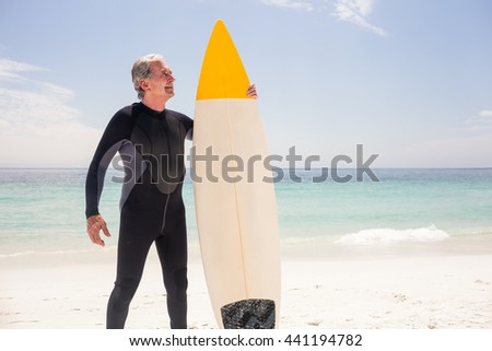 Happy senior man in wetsuit holding a surfboard on the beach - stock photo