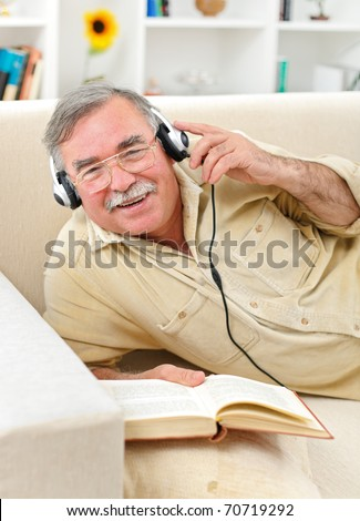 Happy senior man laying on sofa, listening to music while reading
