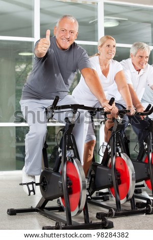Happy senior man on bike holding thumbs up in gym - stock photo