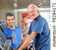 Happy senior man on treadmill with fitness trainer in gym - stock photo