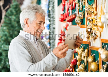 Happy senior man photographing Christmas ornaments through digital tablet at store - stock photo