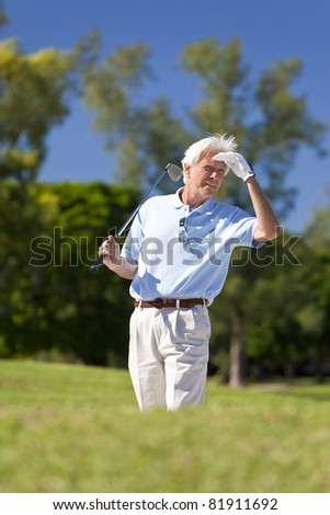 Happy senior man playing golf, standing in a bunker and looking for his ball - stock photo