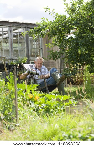 Happy senior man pouring drink while sitting in community garden - stock photo